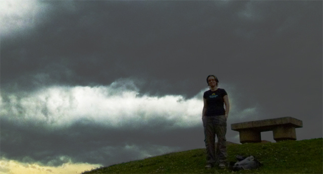 a woman standing on hill before stormclouds