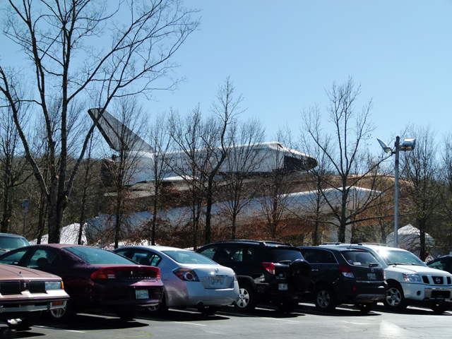 shuttle mock-up behind trees in parking lot