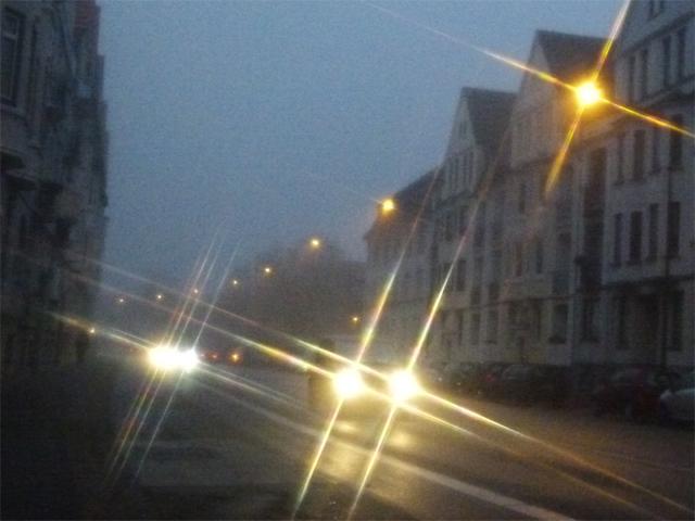 a street with a car, headlights